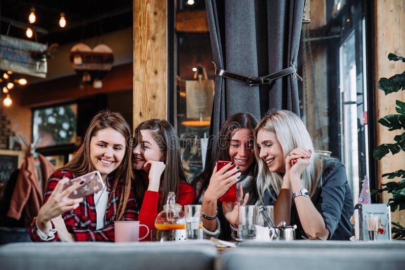 Mujer joven hermosa cuatro que hace el selfie en un café, muchachas de los mejores amigos junto que se divierten imagenes de archivo