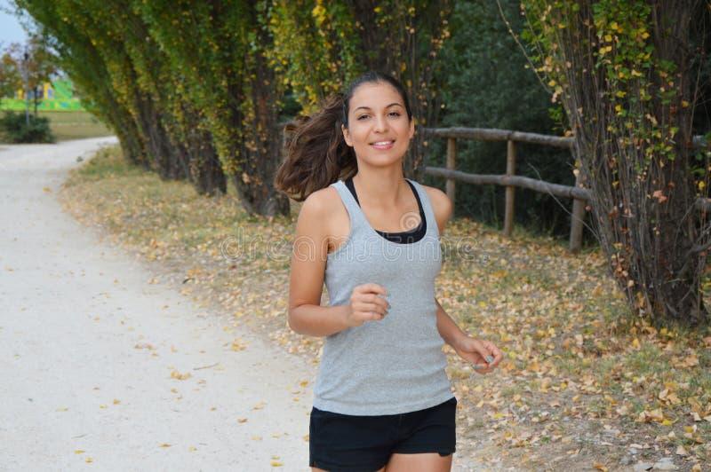 Mujer joven hermosa de la aptitud que corre en el parque Muchacha sonriente que entrena al aire libre foto de archivo