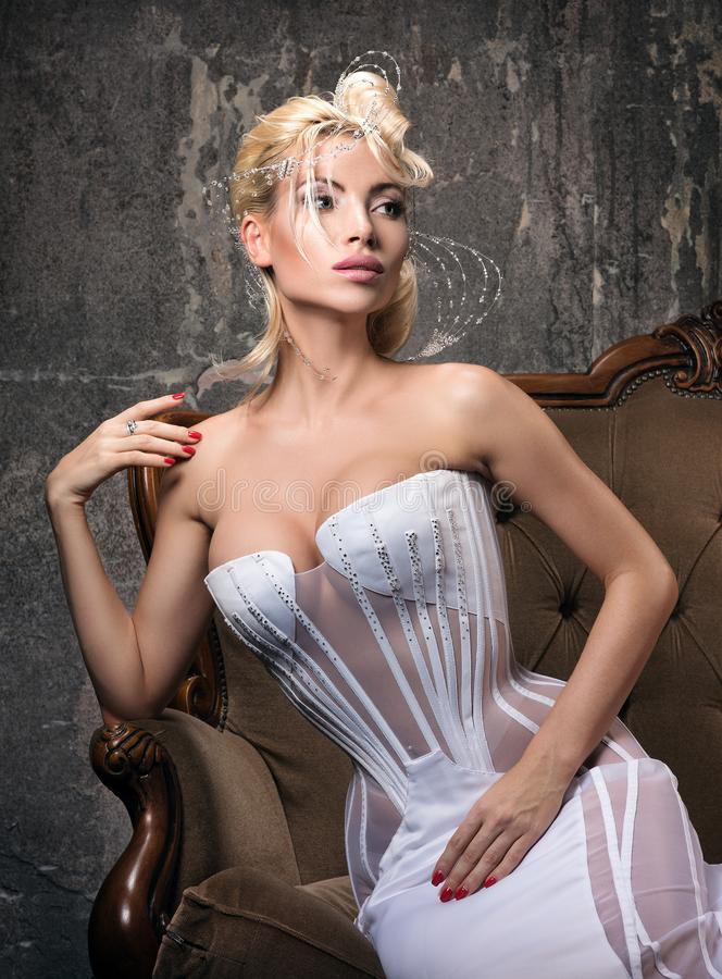 Mujer joven hermosa de la manera vanguardista que se sienta en un sofá clásico imagen de archivo