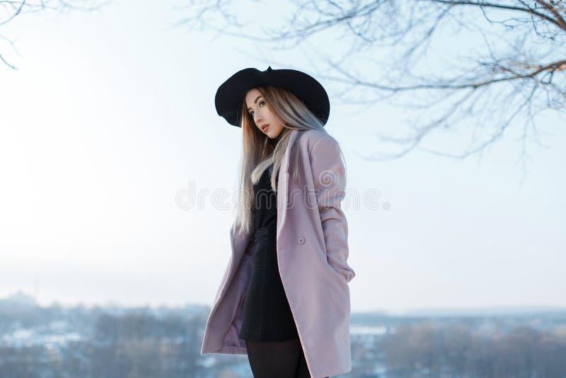 Mujer joven hermosa de moda con el pelo rubio en un sombrero negro elegante del vintage en una capa elegante rosada que presenta  fotografía de archivo libre de regalías