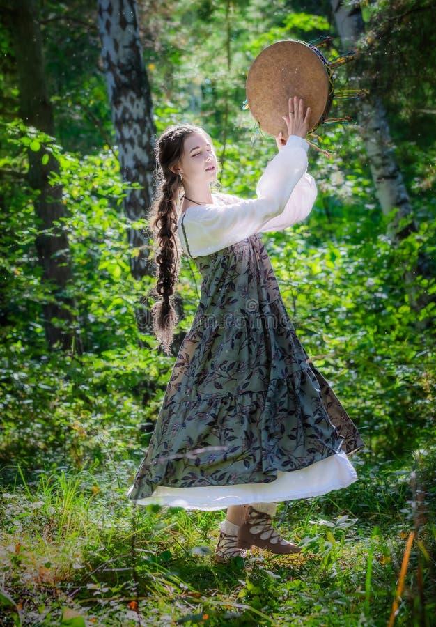 Mujer joven hermosa de una bruja con una pandereta fotos de archivo libres de regalías