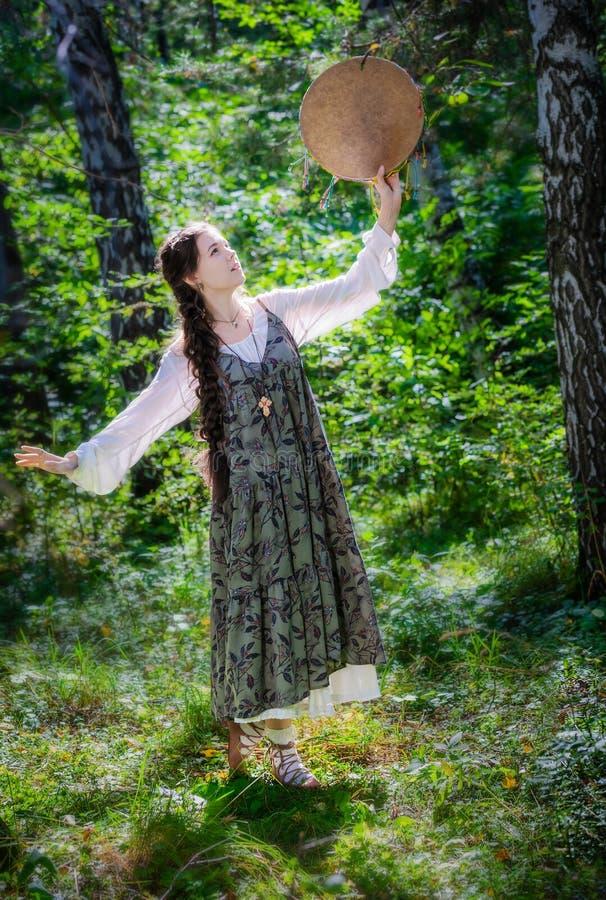 Mujer joven hermosa de una bruja con una pandereta imagen de archivo libre de regalías