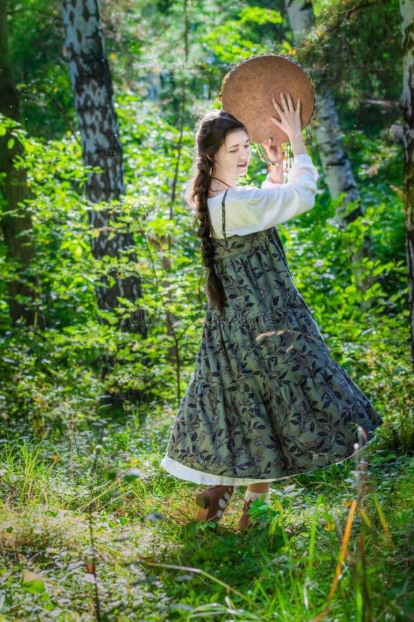 Mujer joven hermosa de una bruja con una pandereta imagen de archivo
