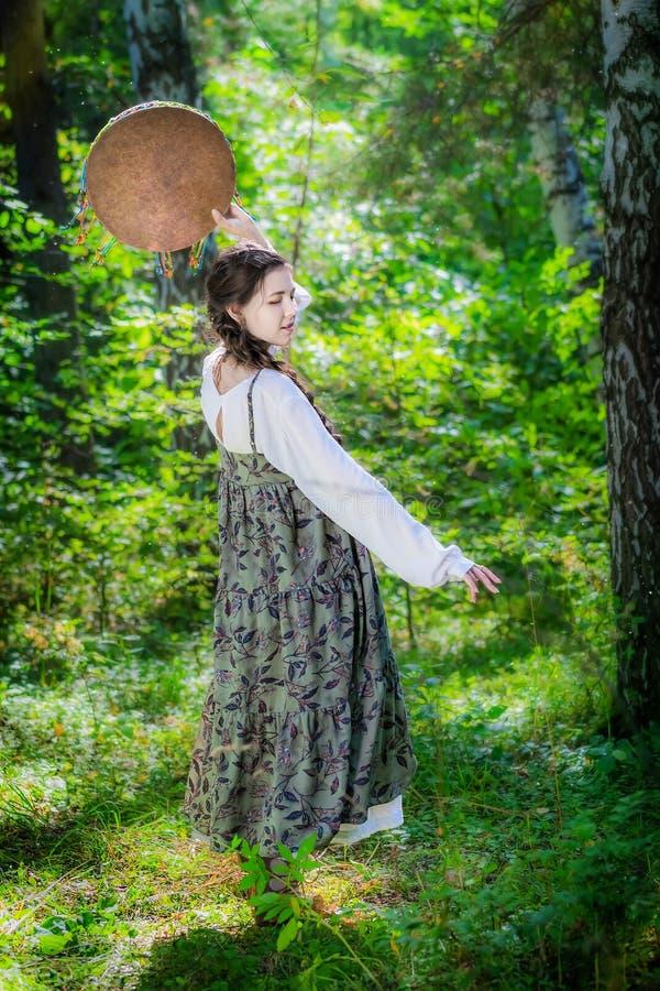 Mujer joven hermosa de una bruja con una pandereta fotografía de archivo libre de regalías