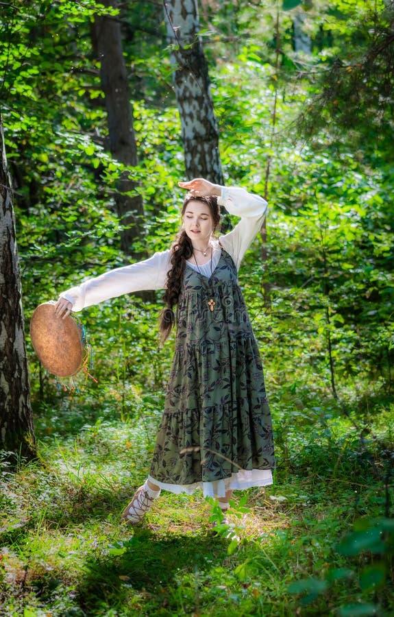 Mujer joven hermosa de una bruja con una pandereta imagenes de archivo