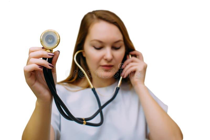 Mujer joven hermosa del doctor que usa el estetoscopio aislado en el fondo blanco Un doctor de sexo femenino con un estetoscopio  imagenes de archivo
