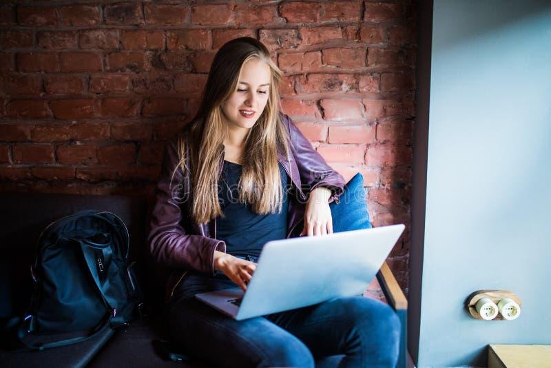 Mujer joven hermosa del freelancer que usa el ordenador portátil que se sienta en la tabla del café Muchacha sonriente feliz que  imagen de archivo