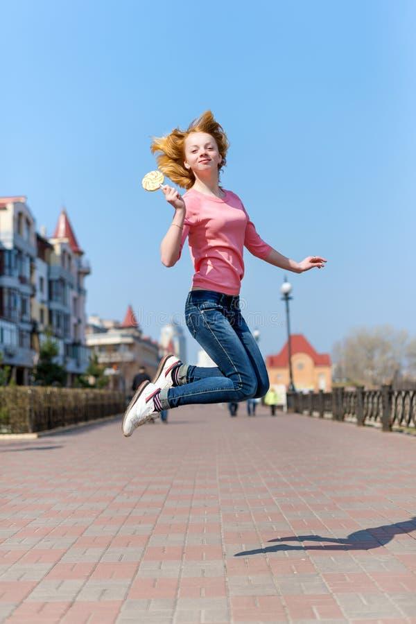 Mujer joven hermosa del pelirrojo que salta arriba en aire sobre el cielo azul que sostiene la piruleta colorida Muchacha bonita  imagenes de archivo