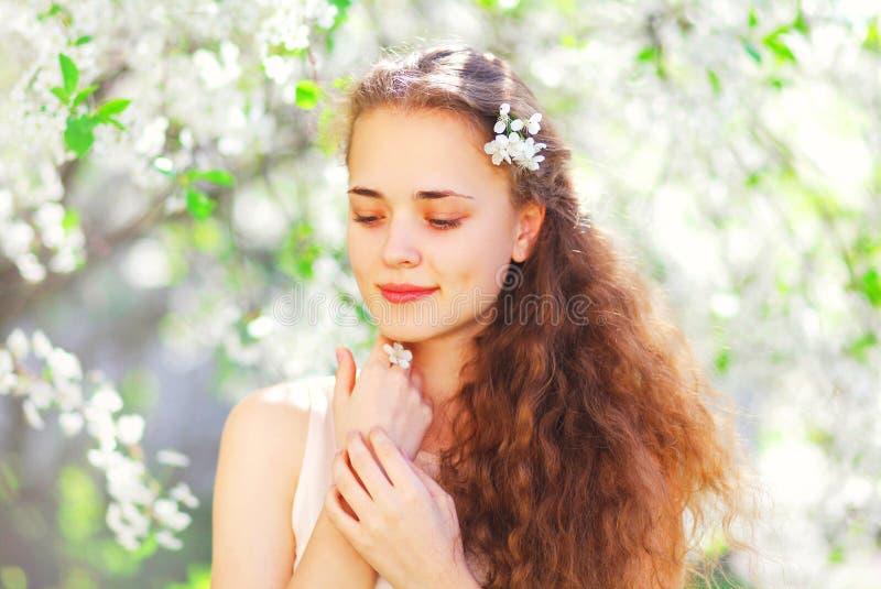 Mujer joven hermosa del retrato sobre jardín floreciente de la primavera fotos de archivo libres de regalías