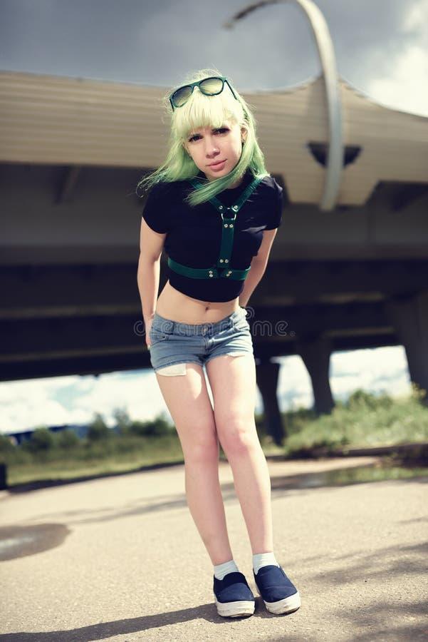 Mujer joven hermosa del swag con el pelo verde que presenta cerca del camino de la carretera imagen de archivo libre de regalías