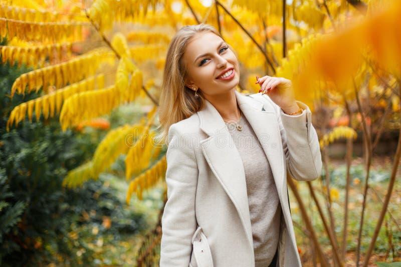 Mujer joven hermosa elegante con una sonrisa en un otoño de moda fotos de archivo
