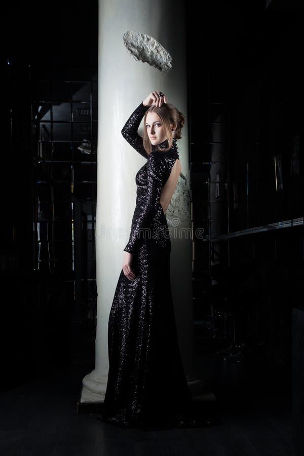 Mujer joven hermosa en alineada negra cerca de la columna imagen de archivo libre de regalías