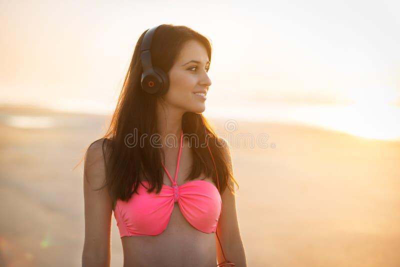 Mujer joven hermosa en auriculares que camina en la playa y enjoing de la música que escuchan foto de archivo libre de regalías
