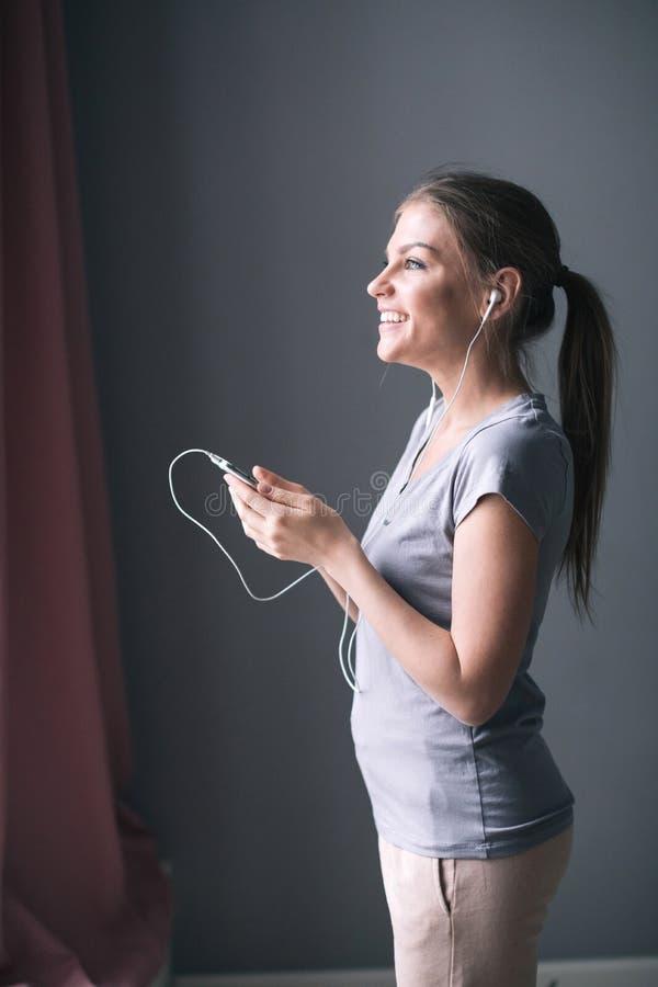 Mujer joven hermosa en auriculares que escucha la música del teléfono móvil en casa imagenes de archivo