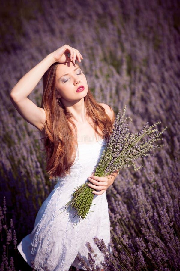 Mujer joven hermosa en campo de la lavanda imágenes de archivo libres de regalías