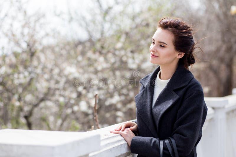 Mujer joven hermosa en capa de lana oscura en la calle en el tiempo de primavera Flores de las flores de la almendra, capa de mod fotografía de archivo