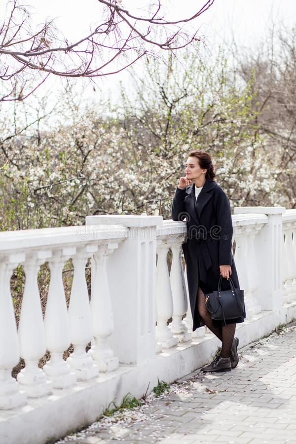 Mujer joven hermosa en capa de lana oscura en la calle en el tiempo de primavera Flores de las flores de la almendra, capa de mod imagen de archivo libre de regalías