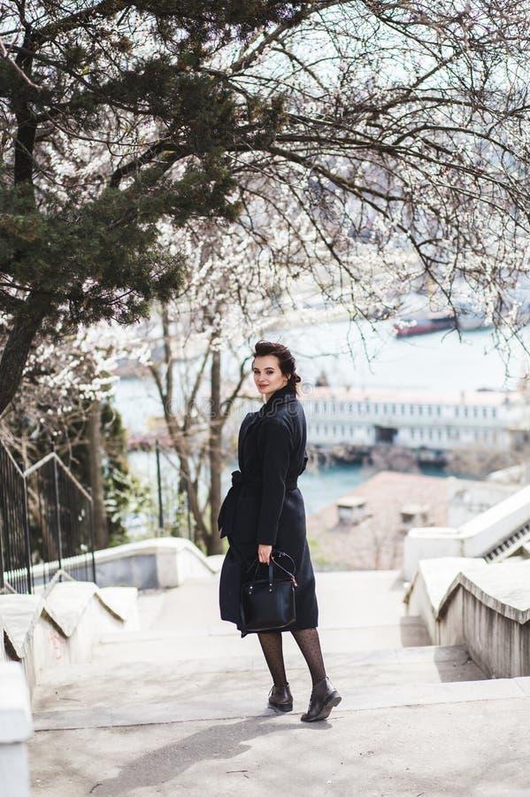 Mujer joven hermosa en capa de lana oscura en la calle en el tiempo de primavera Flores de las flores de la almendra, capa de mod imagen de archivo