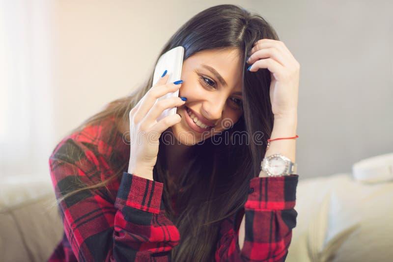 Mujer joven hermosa en casa que se sienta en el sofá y que habla en el teléfono imagenes de archivo