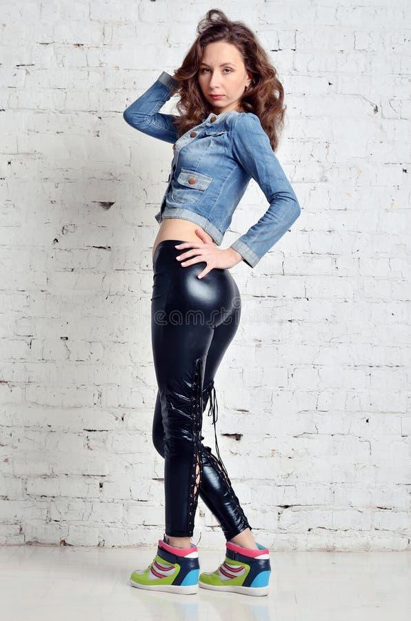 Mujer joven hermosa en chaqueta del dril de algodón y pantalones de cuero negros imagen de archivo libre de regalías