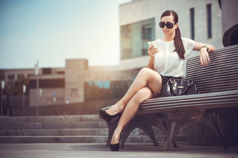 Mujer joven hermosa en el banco imagenes de archivo