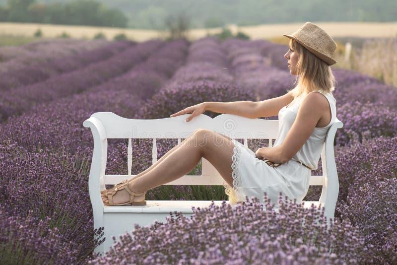 Mujer joven hermosa en el campo de la lavanda en el día de verano caliente imagen de archivo libre de regalías