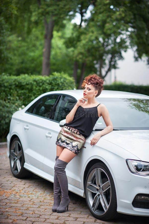 Mujer joven hermosa en el equipo atractivo que se coloca en el coche blanco fotos de archivo libres de regalías