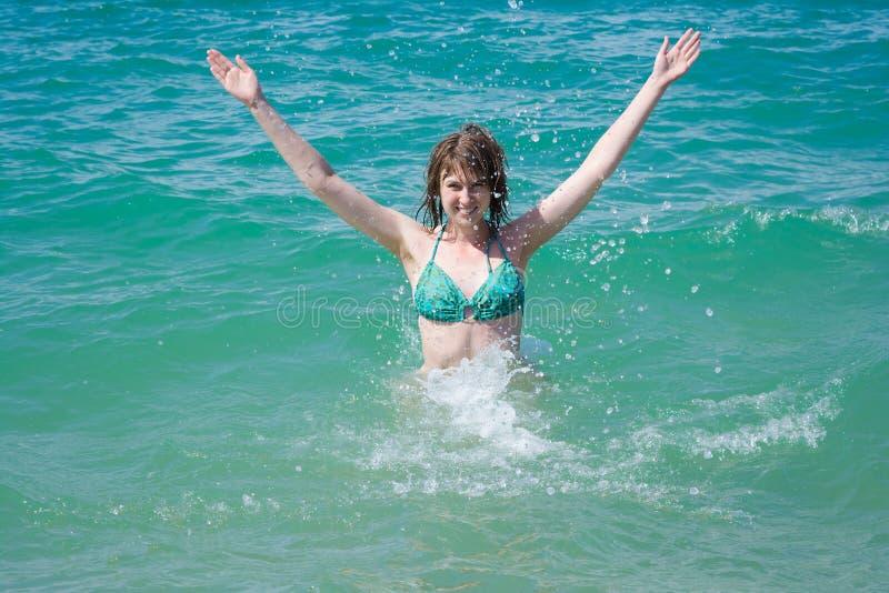 Mujer joven hermosa en el espray del mar imagenes de archivo