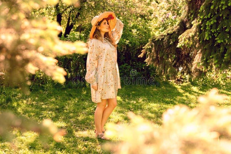 Mujer joven hermosa en el parque Sombrero y vestido ligero del verano mire para arriba imágenes de archivo libres de regalías