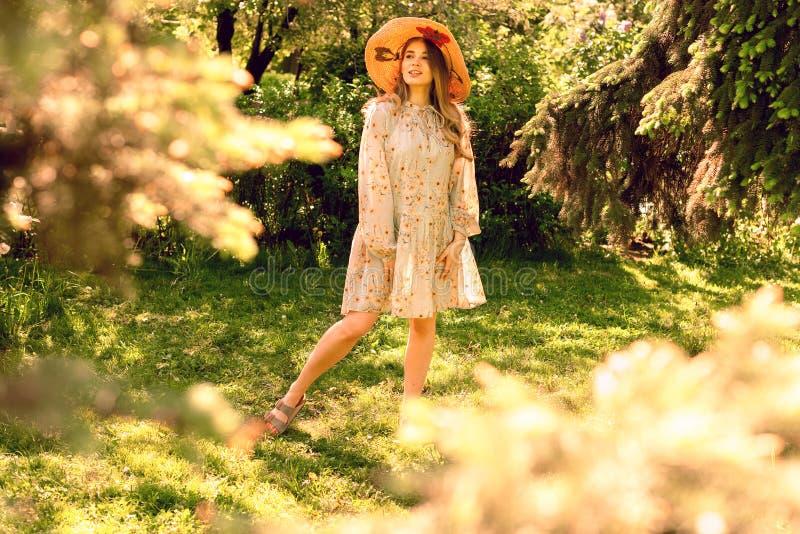 Mujer joven hermosa en el parque Sombrero y vestido ligero del verano imagen de archivo libre de regalías