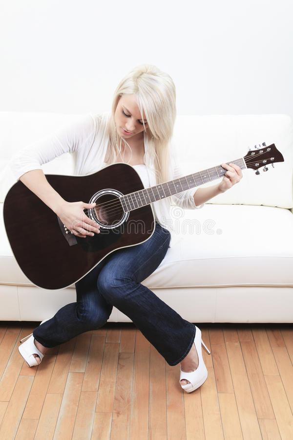 Mujer joven hermosa en el sofá con una guitarra imagen de archivo