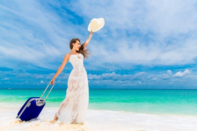 Mujer joven hermosa en el sombrero blanco del vestido y de paja con un suitca fotos de archivo libres de regalías