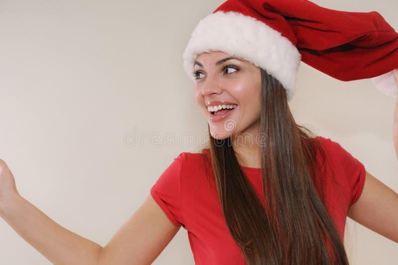 Mujer joven hermosa en el sombrero de Papá Noel muy feliz sobre la Navidad ho imagen de archivo
