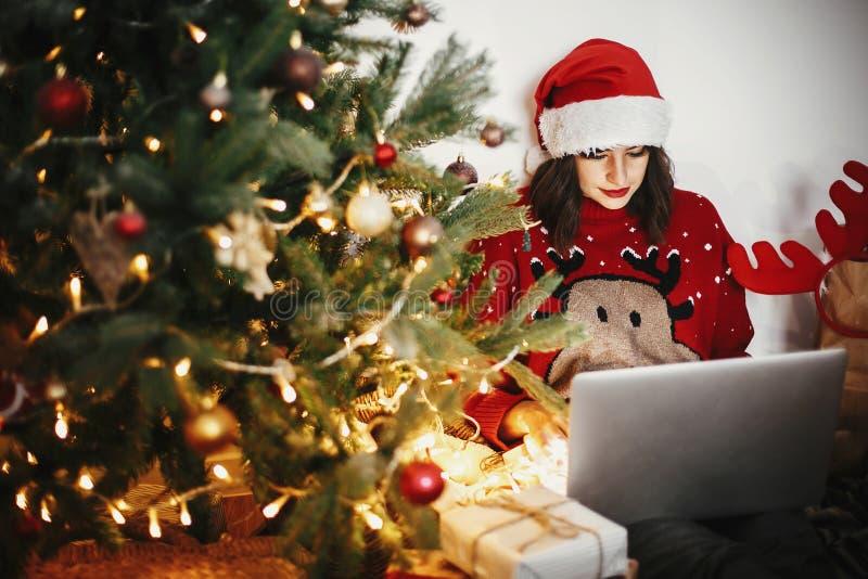 Mujer joven hermosa en el sombrero de santa que se sienta con el ordenador portátil en de oro foto de archivo libre de regalías