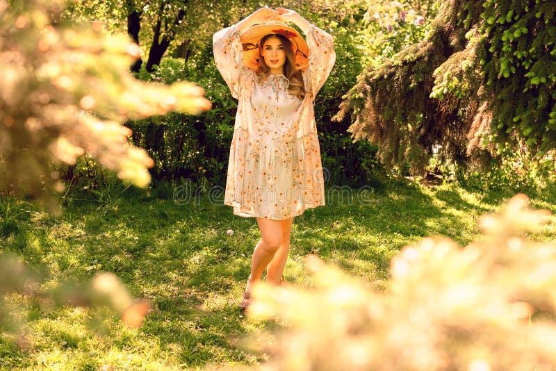 Mujer joven hermosa en el sombrero del bosque y el vestido ligero del verano foto de archivo