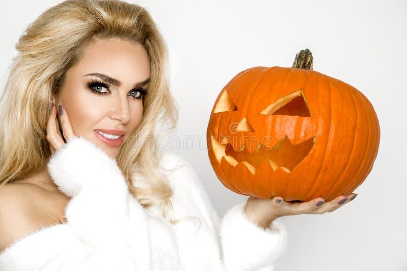Mujer joven hermosa en el suéter blanco, colocándose en el fondo blanco y sosteniendo la calabaza; fotografía de archivo libre de regalías