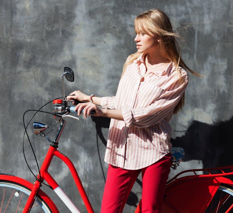 Mujer joven hermosa en el tipo de tela de algodón rojo que lleva a cabo las manos en su bicicleta roja del vintage, oponiéndose a fotos de archivo