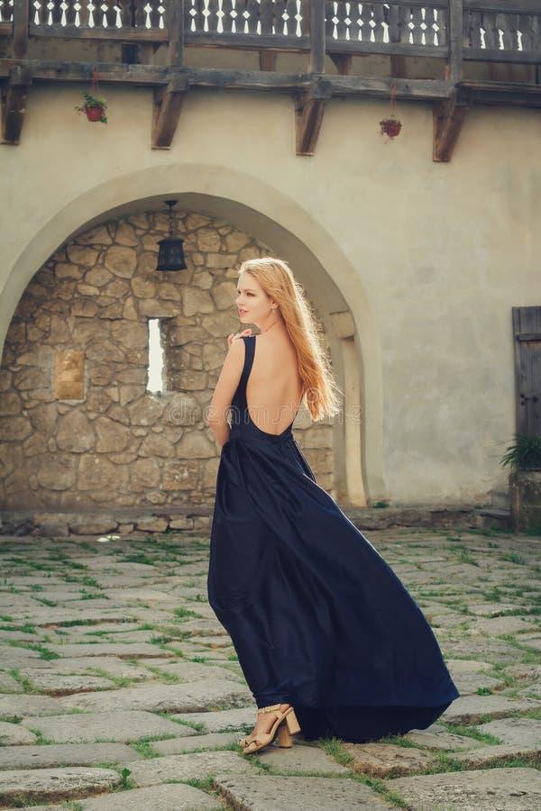 Mujer joven hermosa en el vestido azul que retrocede imágenes de archivo libres de regalías