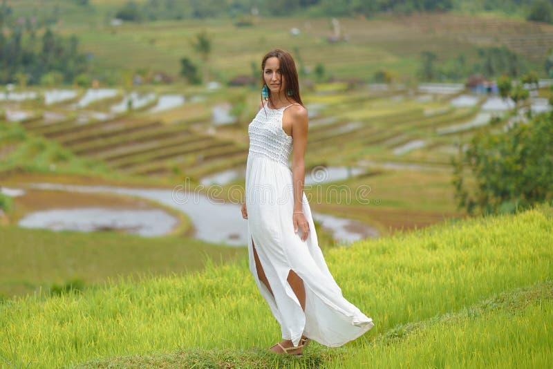 Mujer joven hermosa en el vestido blanco del vintage que camina en campos del arroz imagen de archivo libre de regalías