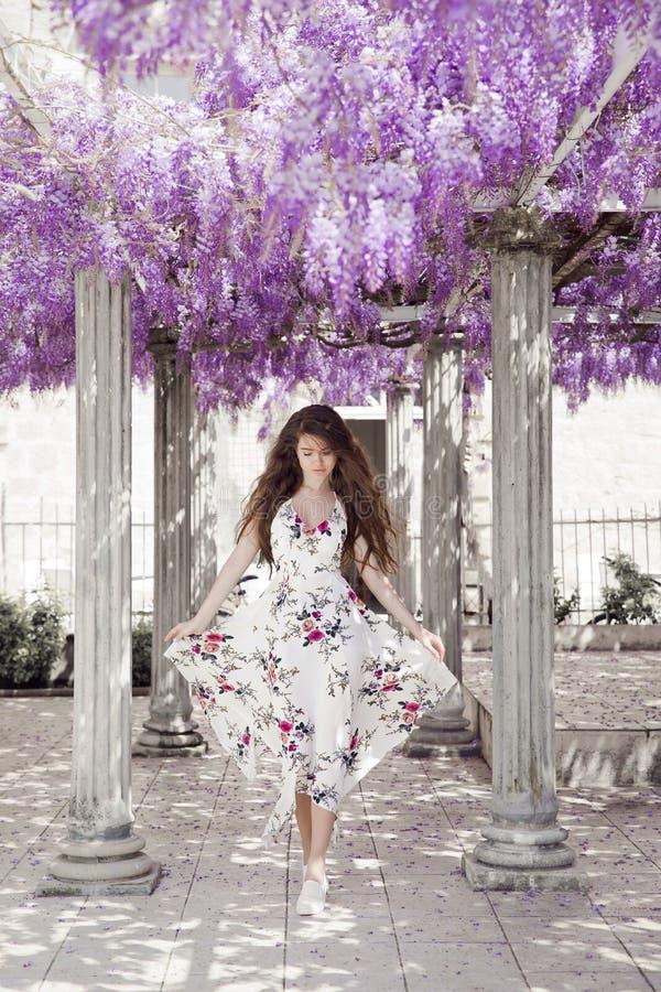 Mujer joven hermosa en el vestido blanco del vuelo sobre el túnel de la glicinia imagen de archivo