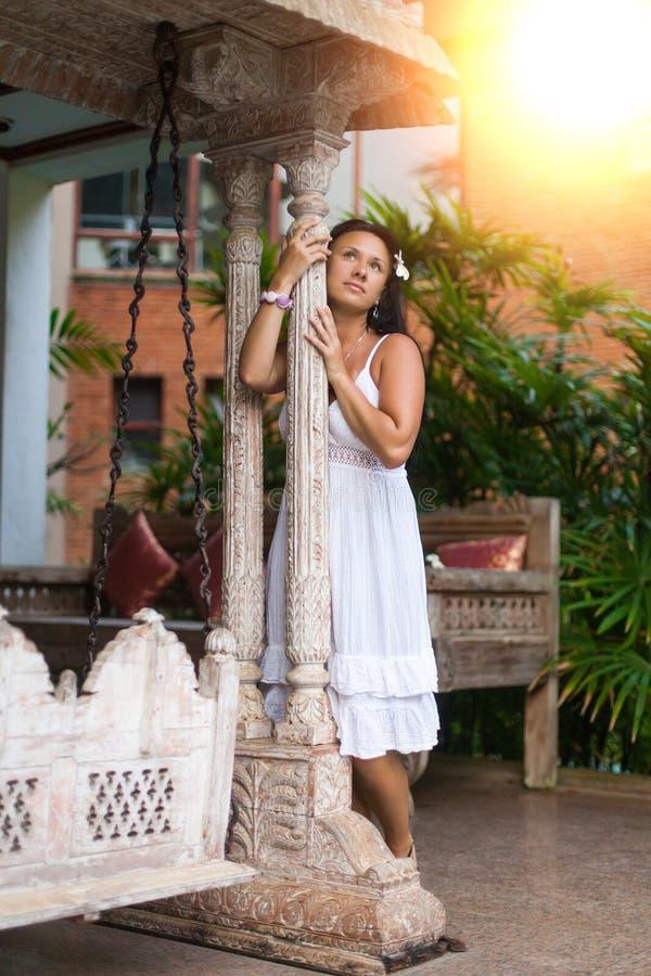 Mujer joven hermosa en el vestido blanco que sueña sobre el oscilación del vintage en jardín Concepto del viaje y del verano fotografía de archivo