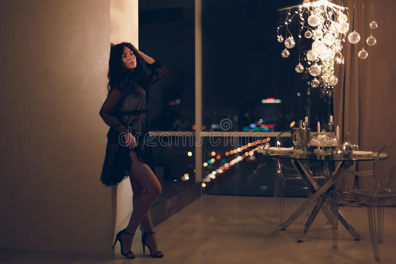 Mujer joven hermosa en el vestido de cóctel negro que se inclina en la pared en la habitación foto de archivo