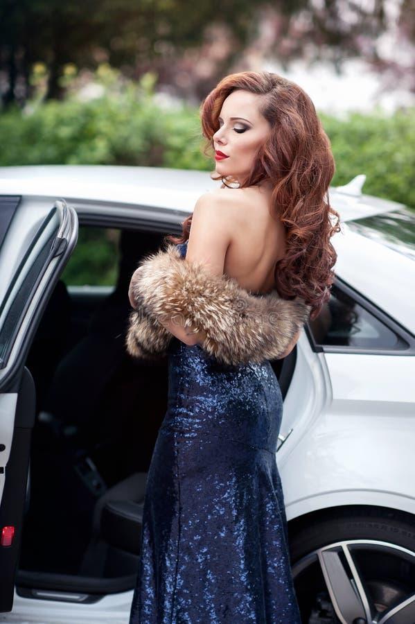 Mujer joven hermosa en el vestido de noche azul que se coloca en imagen de archivo