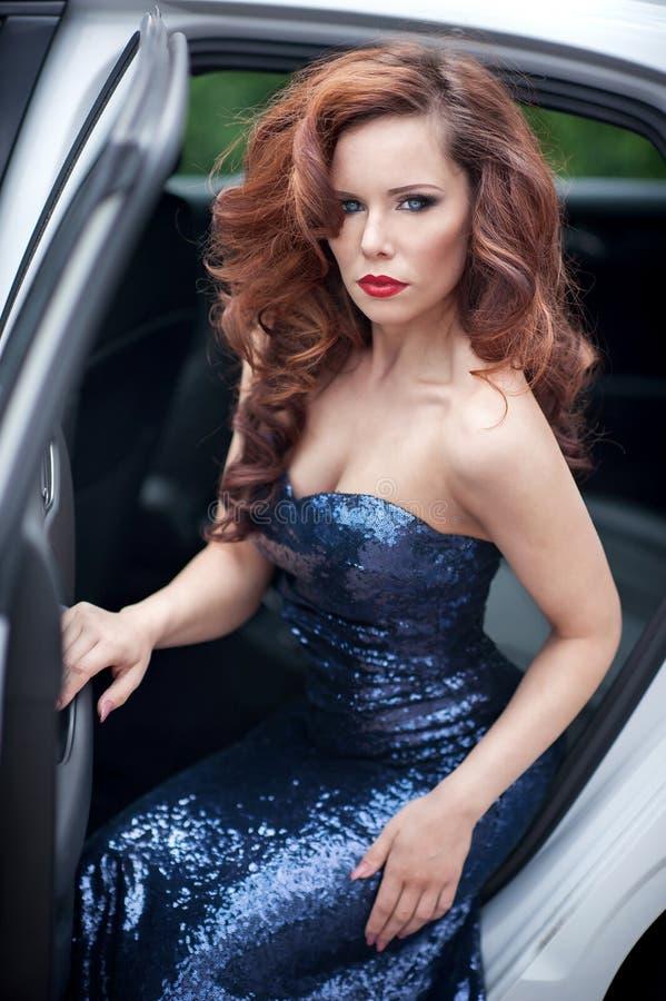 Mujer joven hermosa en el vestido de noche azul que se sienta en el w imagenes de archivo