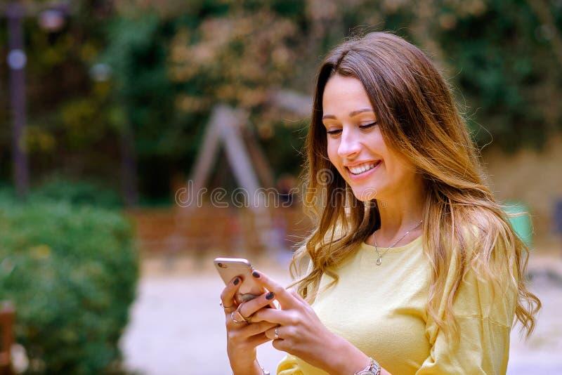 Mujer joven hermosa en equipo de moda que sonríe y smartphone de la ojeada imagen de archivo