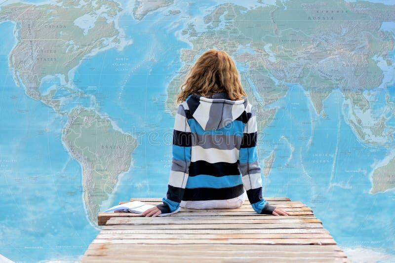 Mujer joven hermosa en fondo del mapa del mundo imagenes de archivo