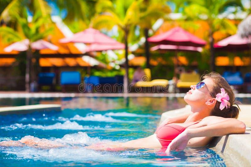 Mujer joven hermosa en gafas de sol en piscina de lujo del balneario imagen de archivo libre de regalías