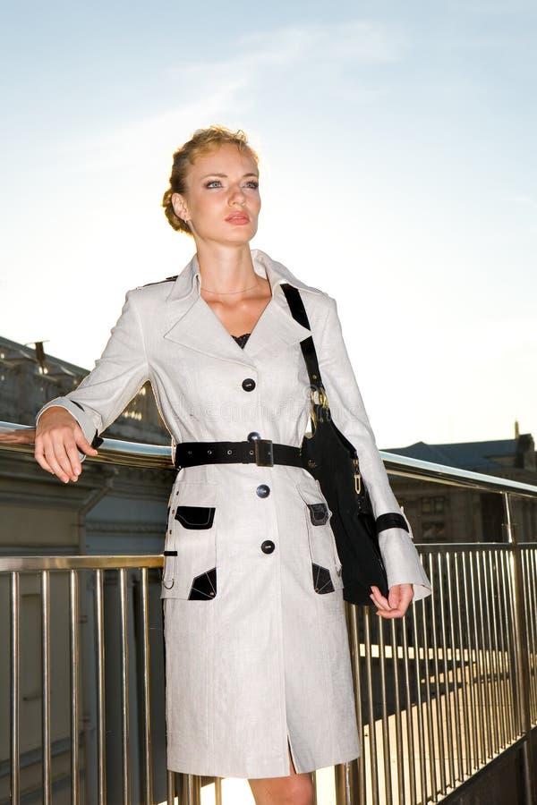 Mujer joven hermosa en impermeable ligero imagen de archivo