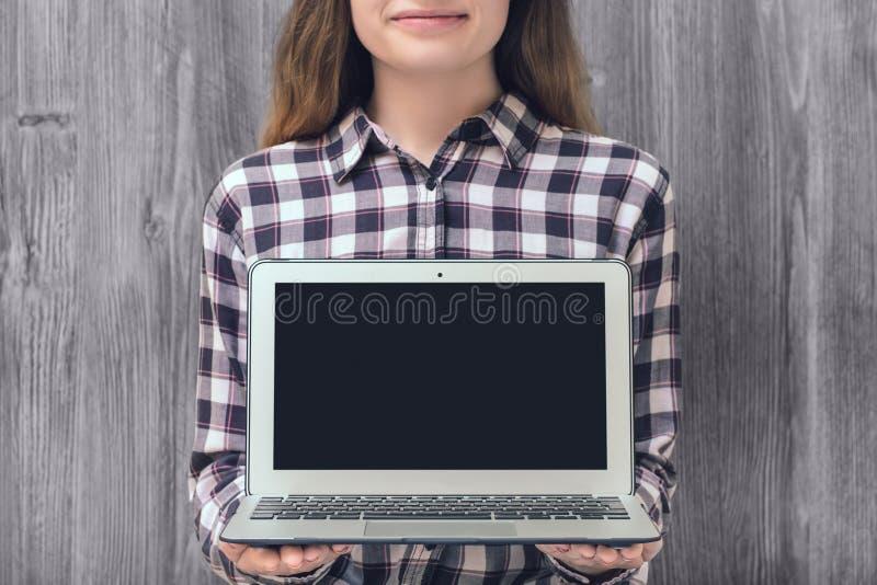Mujer joven hermosa en la camisa a cuadros que muestra la pantalla vacía encendido imagenes de archivo