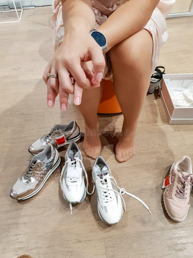 Mujer joven hermosa en la falda y el panty que intentan en los nuevos zapatos en centro comercial imagenes de archivo